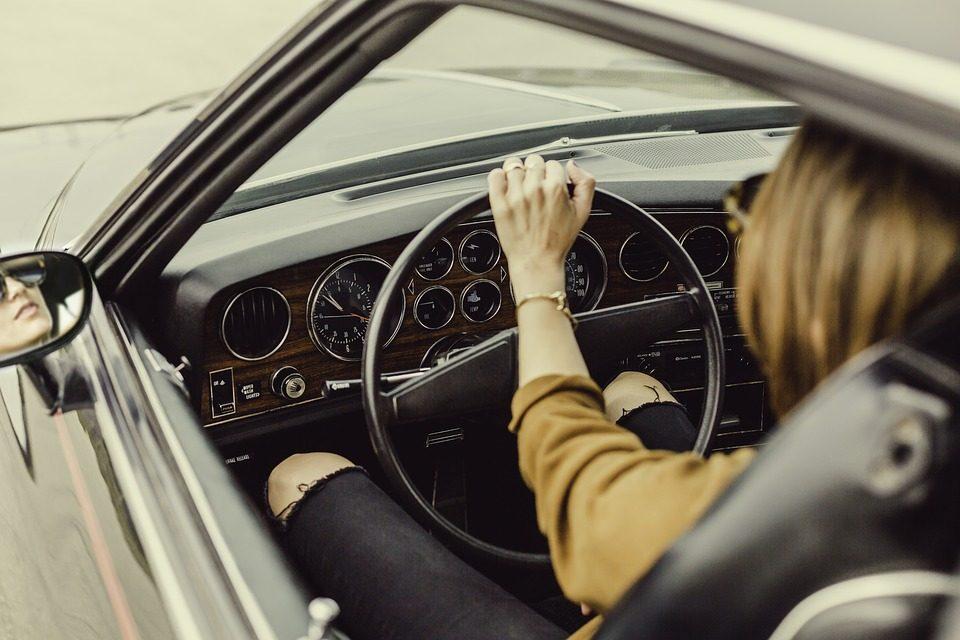 Imagem de uma mulher ao volante de um belo automóvel antigo Interatividade Corretora de Seguros