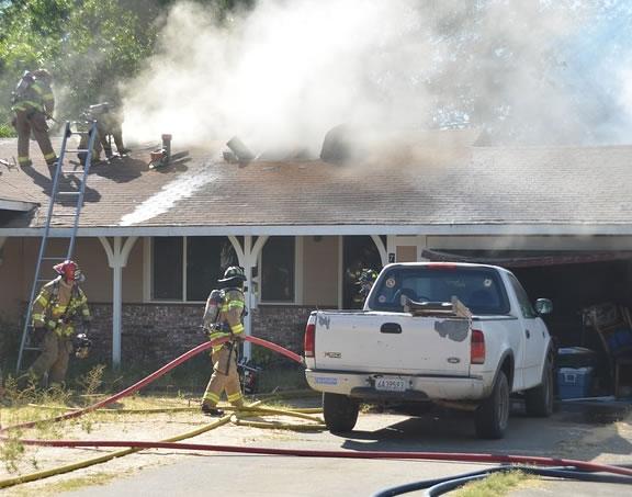 fotos de bombeiros apagando um incêndio em uma casa.