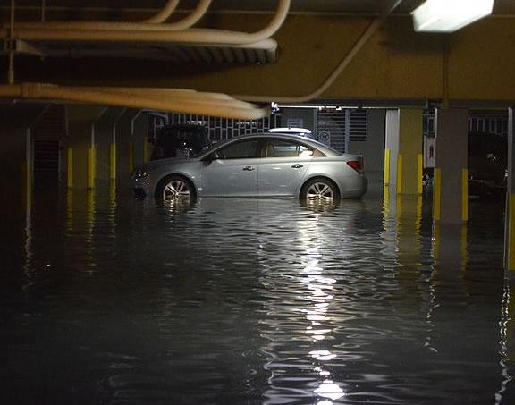 Foto de um carro dentro de uma garagem de condomínio alagada, representando a importância do seguro condominial Interatividade Corretora de Seguros