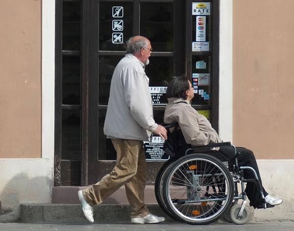 Foto de um homem empurrando uma mulher na cadeira de rodas, representando o seguro invalidez - Interatividade Corretora de Seguros